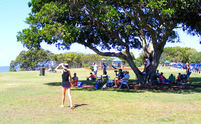 People relaxing at the park in Nudgee Beach