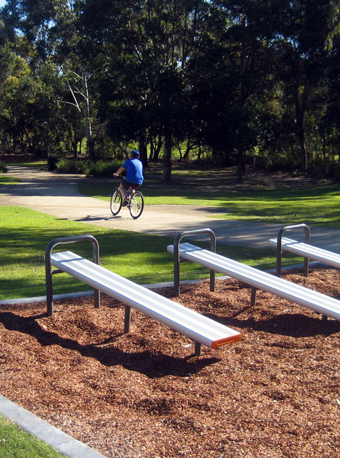 Cyclist rides past exercise equipment in North Lakes