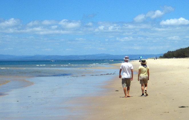 A couple walking along the Red Beach in Bribie Island