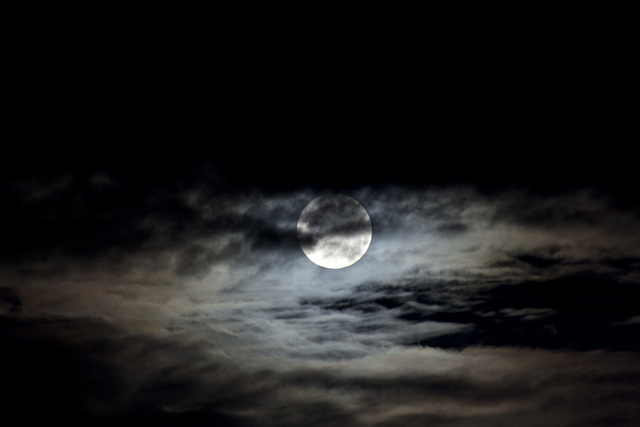 A supermoon peaking through the clouds (Attribution: Flickr - Jim H.)