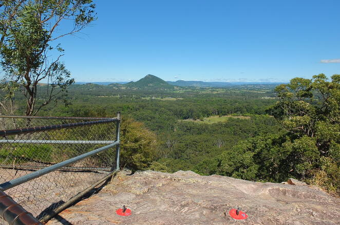 Mount Tinbeerwah Lookout Track, Tewantin National Park, adventurers, 360 degree views, Noosa region, hinterland, Pacific Ocean, locals, tourists, Noosa Heads, paved pathway, handrails, rest seats, wheelchair and pram access, one kilometre return, 45 minutes, pack a picnic, sunset thrill-seekers, abseiling, rock climbing, wildlife, yellow-tailed black cockatoos, lizards, snakes, Montane shrubland, wildflowers in bloom, various trail options from foot of Mount Tinbeerwah, Wooroi day-use area, mountain bikers, no fresh water, spectacular views