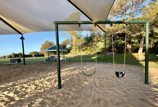 The small playground also includes more traditional equipment such as these swings