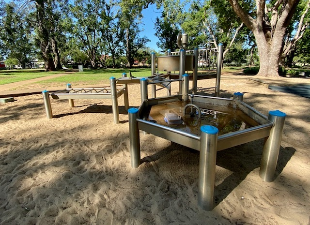 A water play area set under the shade of beautiful trees