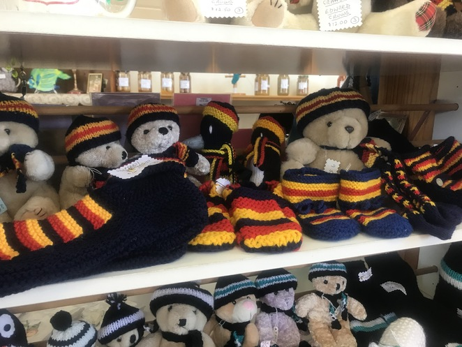 Knitted teddies and teddy-clothes in footy colours