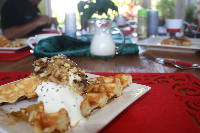 Homemade waffles dripping with maple syrup and yogurt with walnuts on top.