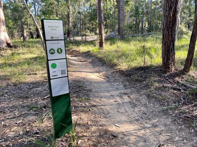 Trailhead signs include QR codes to download a map of the tracks