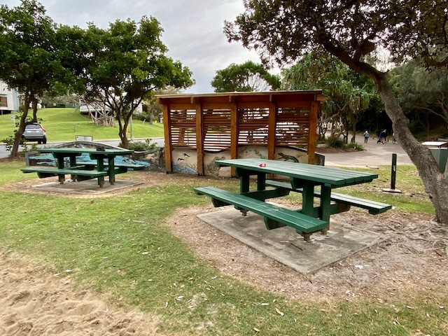 Picnic tables between the bus stop and the playground at Headland Park