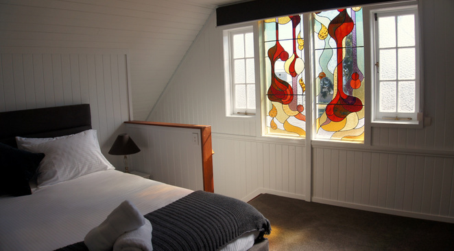 The bedroom loft has a stained glass window