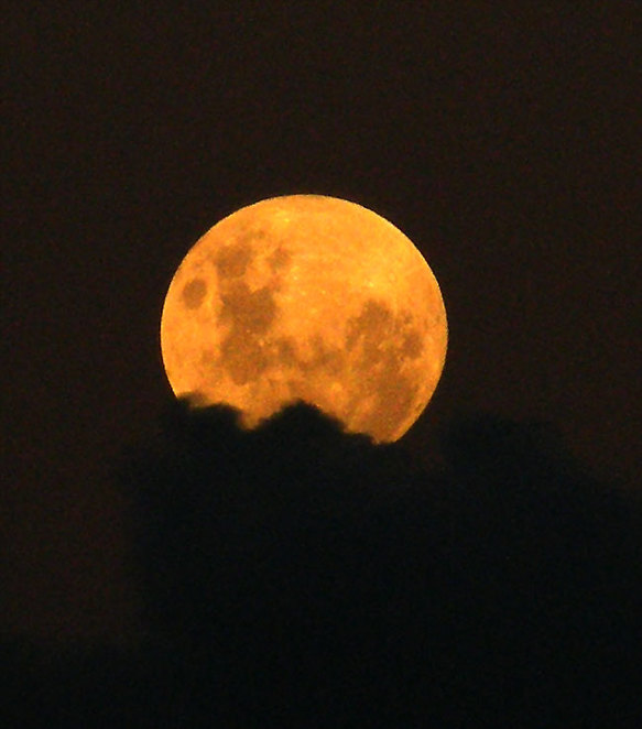 A full moon rising from behind a cloud