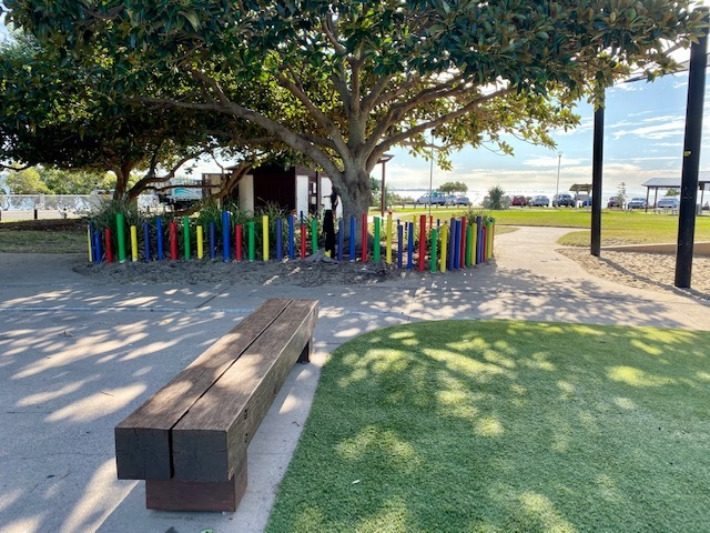 Shaded seating in the playground with public amenities in the background
