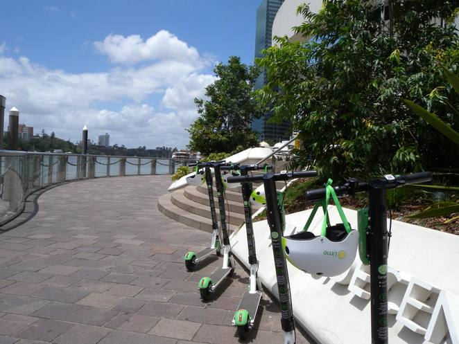 A cluster of Lime Scooters. Note: Not all have helmets.