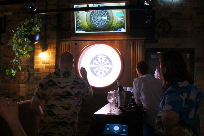 Play darts with your friends in a booth with seats and tables at Oche