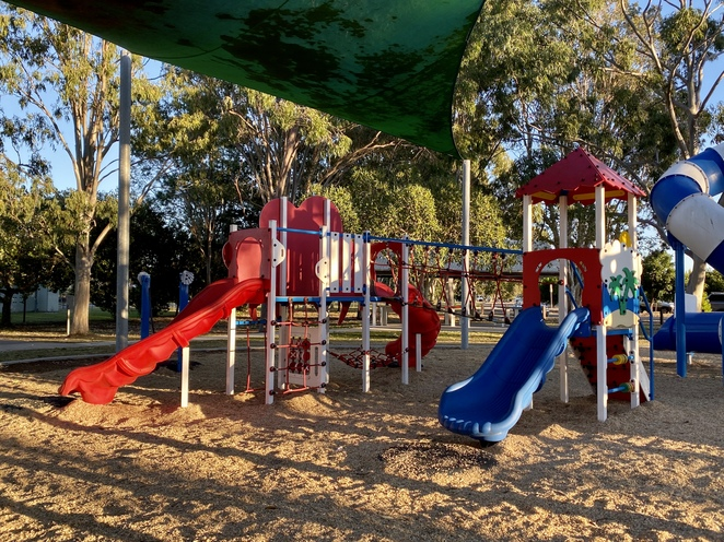 A smaller playground sits under shade sails beside the large tower structure