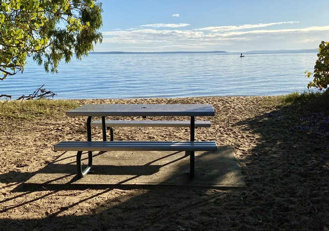 A picnic table overlooking Morwong Beach at high tide