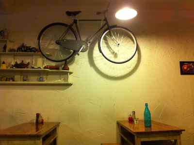 A bike is pinned to the side of the wall, Clipper Cafe
