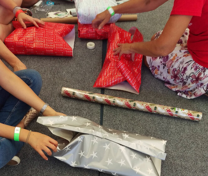 Presents being wrapped to be given to kids in need