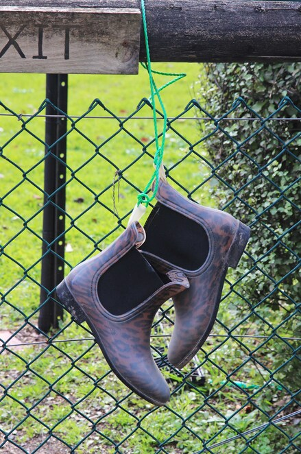 Boots hanging on fence.