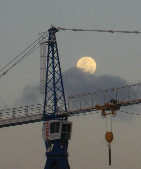 Moonrise behind a crane