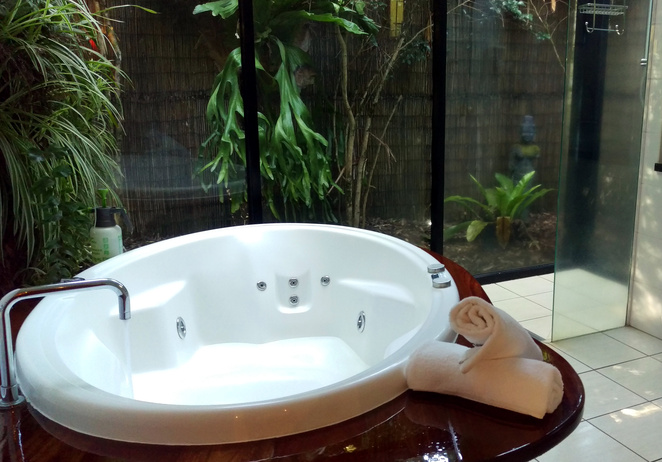 Relax in a spa bath in a rainforest garden