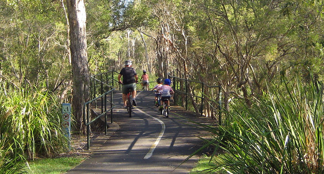 A family cycling at the Boondall Wetlands
