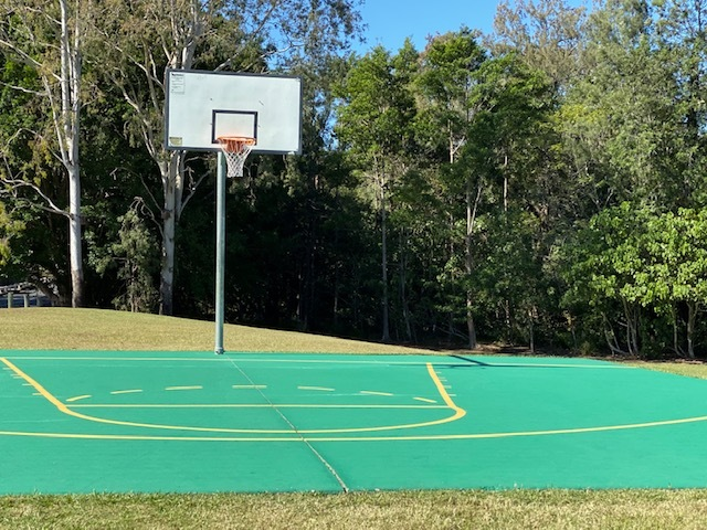 Basketball half-court between grassy playing areas