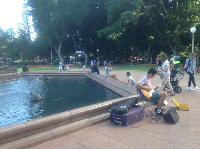 Hyde Park Sydney Busker at fountain people walking through