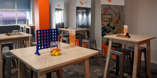 The reception area has chairs, tables, sofas and games while you wait