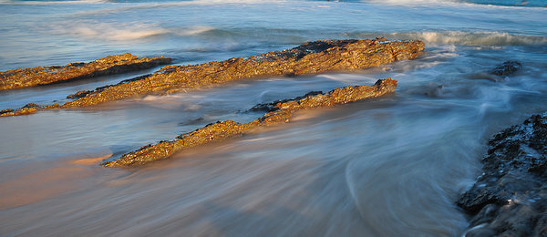 Waves flowing across the base of Currumbin Rock at sunrise