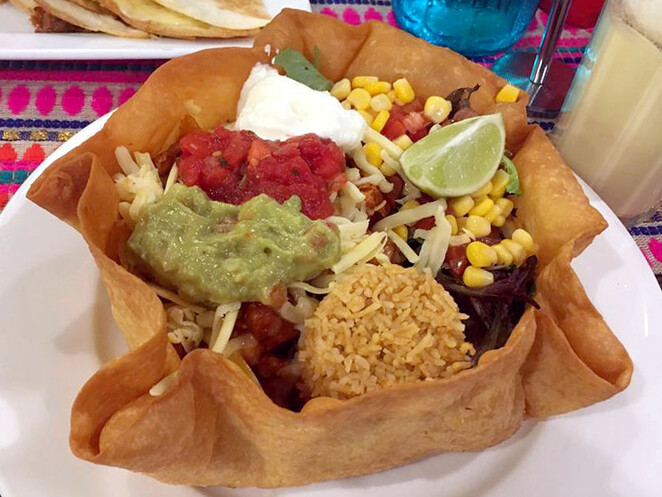A tostado is food served in a deep fried taco bowl