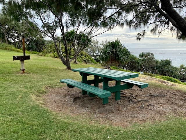 One of the picnic tables with a BBQ overlooking the ocean at Mulumba Park