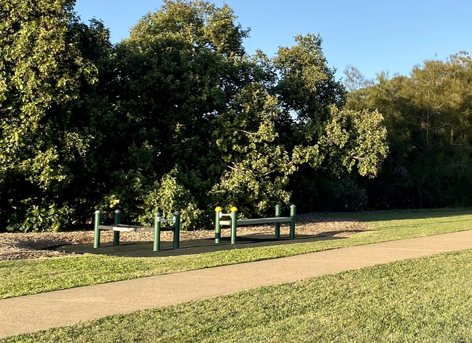 Additional outdoor gym equipment is installed along the pathway in this part of the reserve