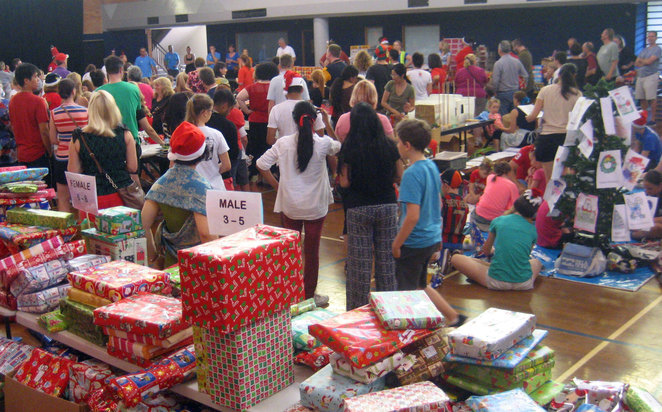Volunteers putting together packages of food and presents for needy families at Christmas