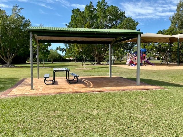 Shaded picnic area set between the basketball court and the playground