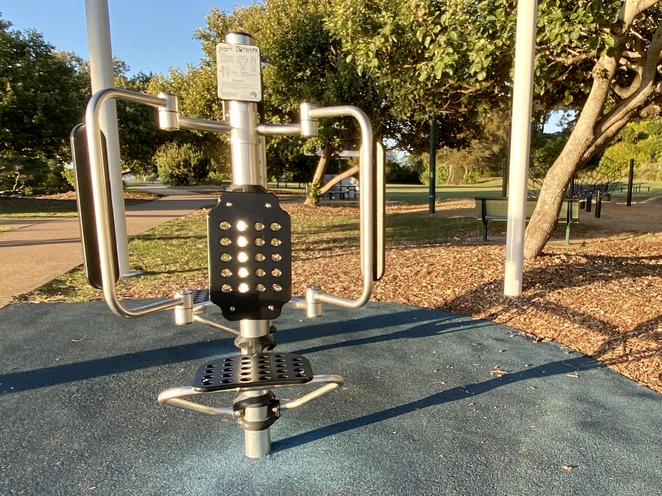 A small but modern outdoor gym area sits between the canoe launch area and a playground