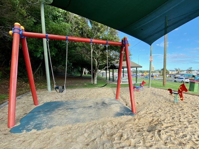 Swings for toddlers and older kids are installed above soft-fall surface