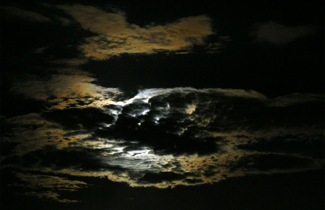 The moon hiding behind some clouds