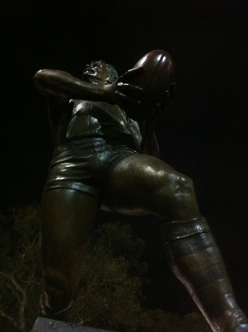 Can you guess who this person is, and which famous Melbourne landmark he stands outside of?