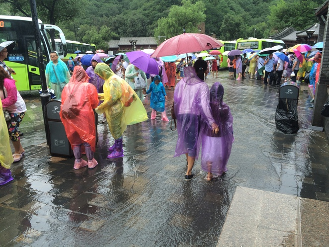 Lots of people, buses, hawkers, maybe even a torrential downpour