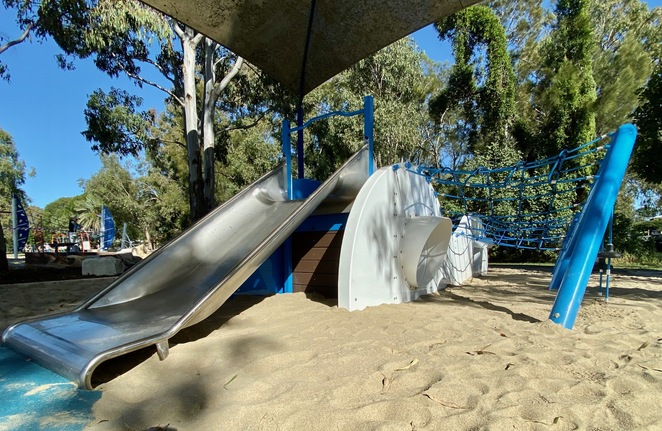 A smaller climbing structure with rope challenges and a small slide sits under a shade sail