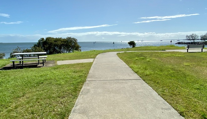 A bike and foot path leads down to a small sandy beach and the edge of Moreton Bay
