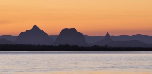 The Glasshouse Mountains across the Pumicestone Passage at sunset