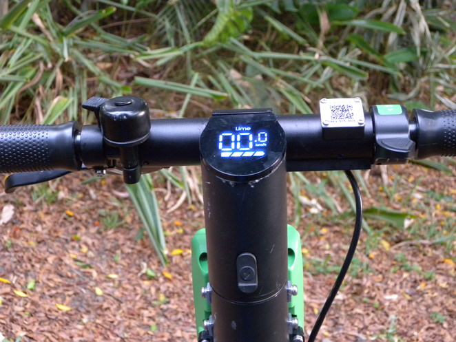 The left handlebar has a hand brake attached. Next along is the bell, then the speedometer, the QR Code, the accelerator tab, and the right handlebar.