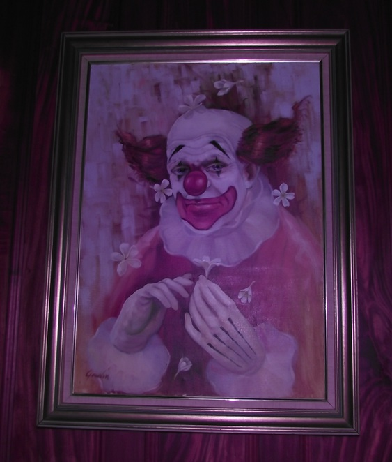 Spooky Clown Paintings line the wall of the dining room