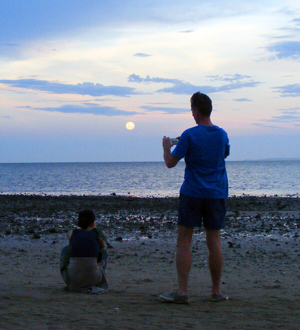 Photographing the moon at the beach while the sky is still light