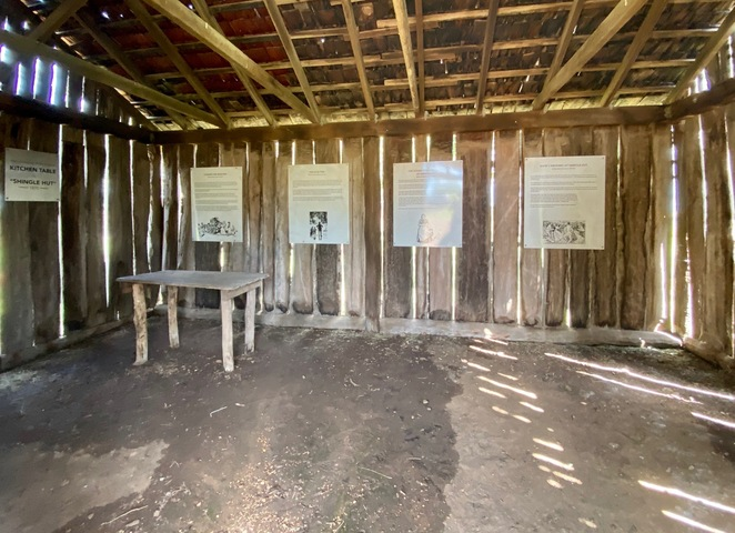 The inside of the replica shingle hut includes interpretive signs for guests