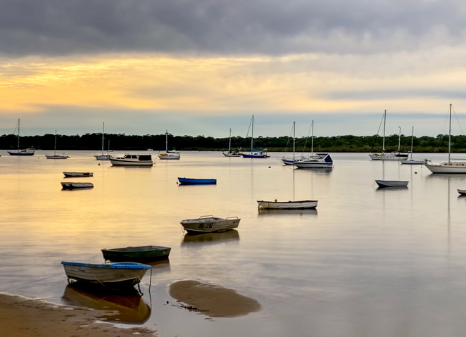 A long exposure with the boats in the foreground resting on the sand for stability