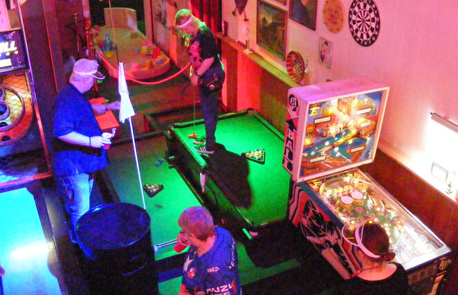 To play this hole at Holey Moley, you have to first put the golf ball in the pin ball machine, which shoots it onto the pool table, then you pocket the ball which then lands on the lower pool table