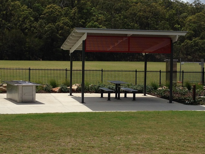 shady barbecue area with tables and seating